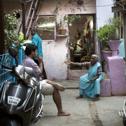 A worker watches his neighbourhors chat on a porch. Back alleys are full of a variety of uses. Homes themselves often double up as work spaces. (Photo by Ishan Tankha for urbz).