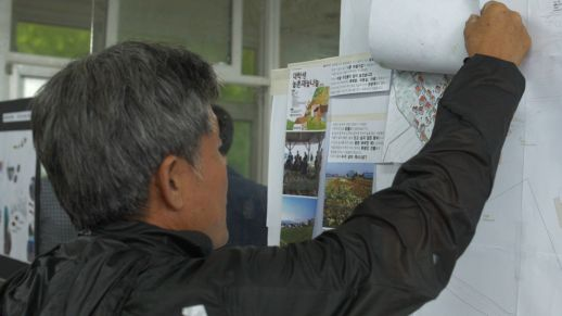 Visitors examine the proposals that are exhibited.