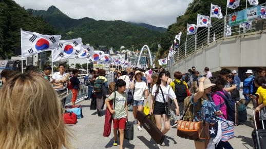 Arrival at Dodong port, lined with Korean national flags and thronged with tourists.