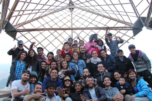 The entire team involved in the workshop with the structure installed in the background