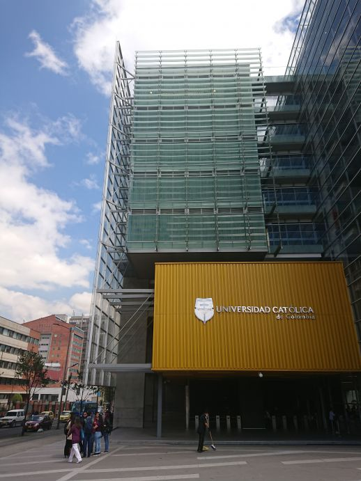 A building of the Universidad Catolica de Colombia with a glass façade can be seen with a building with an exposed brick façade in the background