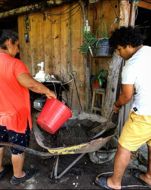 Tobias and Lucina mixing and pouring gravel and cement to temporarily repair damage caused by floods to the patio of Lucina's home