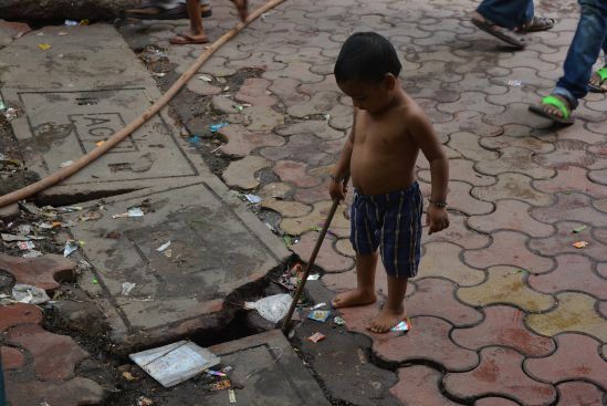 A kid playing with a stick in the gutter at Bareilly Compound.
