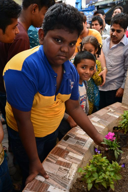 Kids planting flowers as a symbolic gesturing expressing their desire for the improvement of the space where they meet and play. Far left, Gulzar Khan, Waqar's son.